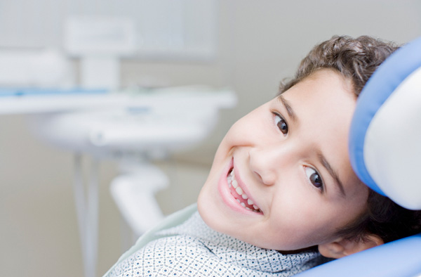 Young boy smiling with healthy teeth after getting dental sealants at Ford Dental Group in Huntington Beach, CA